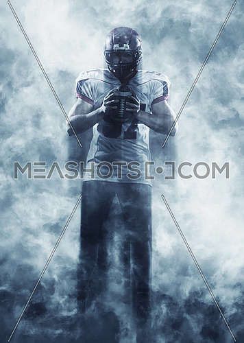 portrait of confident American football player holding ball while standing on the field with smoke effect around