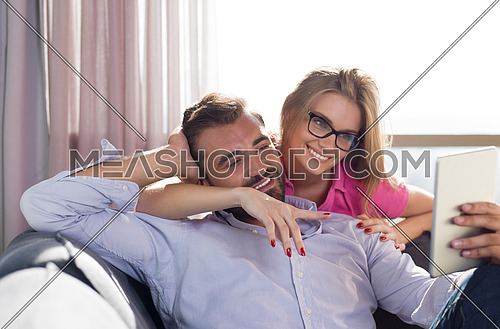 Young couple relaxing at  home using tablet computers reading in the living room on the sofa couch.