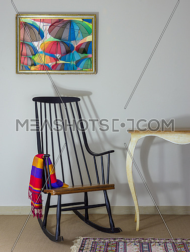 Classic rocking chair and off white vintage table on background of off white wall with hanged painting including clipping path for painting
