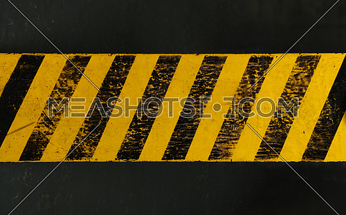 Old yellow weathered painted background with grunge black hazard sign stripes over dark