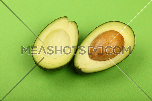 Two halves of one fresh ripe cut avocado with pit stone on green paper background, detail, close up, high angle view