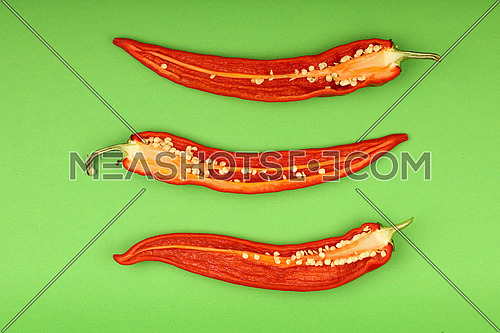 Three cut halves of fresh red hot chili peppers on green paper background, close up, elevated top view