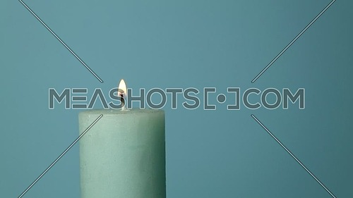 Close up one blue candle trembling flame over light blue background, off-center, fired up with lighter, burning and blown out, low angle side view