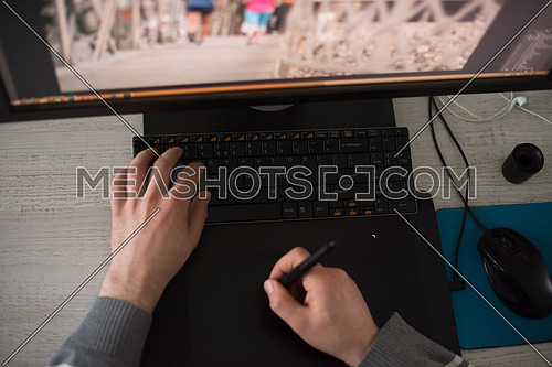 Young graphic designer working on a digital tablet and a computer top view