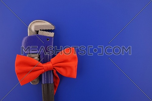 Pipe wrench tied with a red bow over a blue background with copy space. Labor Day or fathers day concept