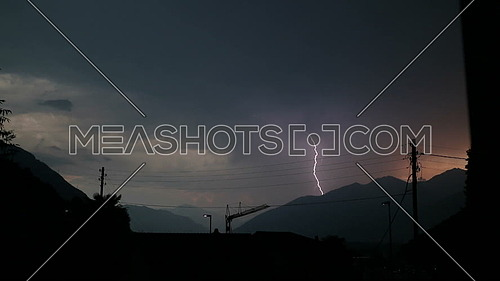 Lightning strike in a thunderstorm over city roofs in the mountains