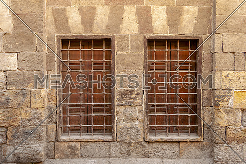 Two similar adjacent wooden windows with iron grid over decorated stone bricks wall, Medieval Cairo, Egypt