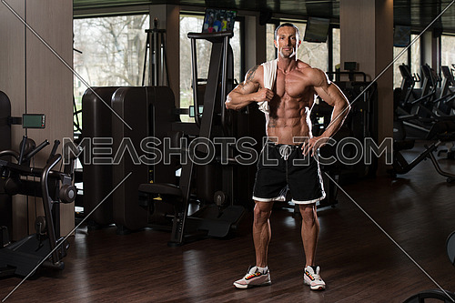 Handsome Muscular Man With A Towel On His Shoulders In Modern Fitness Center