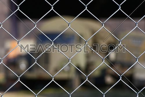 Old military transport truck as a background behind a chain link fence at an army depot