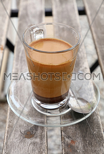 Turkish freshly brewed natural ground coffee with milk in transparent full glass cup with saucer over vintage wooden table, close up, high angle view
