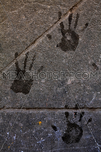 Hand marks on a dusty concert wall