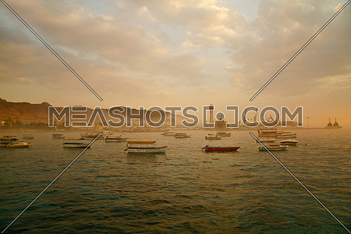 super wide shot on sunset for red sea , showing small boats , port in the background , cloudy sky .