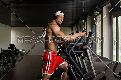 Muscular Mature Man Doing Aerobics Elliptical Walker In Modern Fitness Center