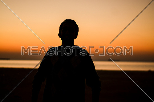 silhouette of man on the beach during sunset