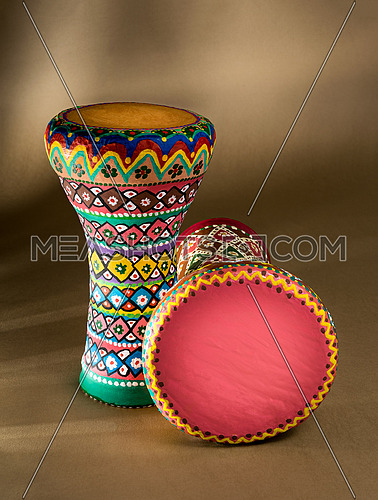 Two decorated colorful pottery goblet drums (chalice drum, tarabuka, darbuka) on background of wooden table with vanishing shadow lines. Low light