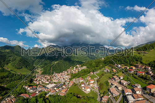 Drone aerial view to the Seriana valley and Orobie Alps with big cloud and blue sky
