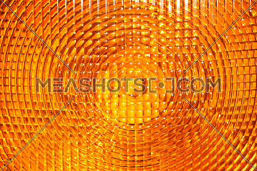 Abstract background of vivid yellow orange faceted plastic reflective surface sign or rear lamp of taillight