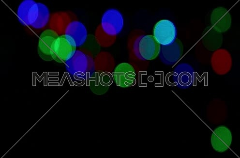 Colorful multicolor festive Christmas circular bokeh over dark, blue, green and red lights slow moving trembling and shaking, abstract background