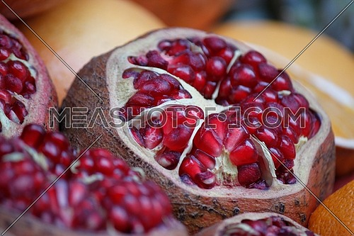 fresh pomegranate in the market sliced showing the seeds ready to be squeezed