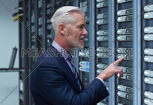 Portrait of senior businessman working in big rack server room