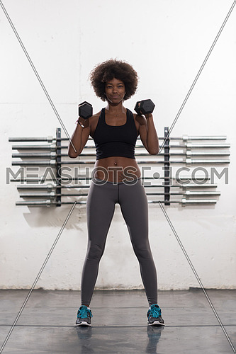 young beautiful African American woman doing bicep curls in a gym