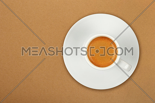 Close up one white cup full of espresso coffee on saucer over brown paper parchment background, elevated top view, directly above