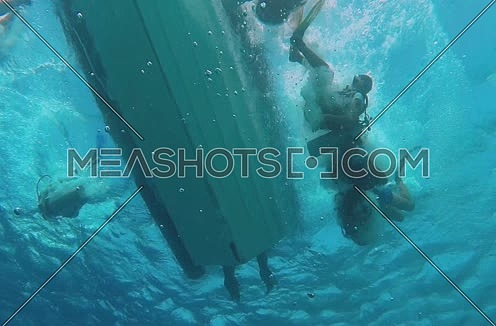 long shot underneath a Motor boats and divers are jumping into water at the Red Sea