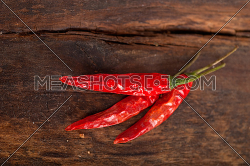 dry red chili peppers over old wood table