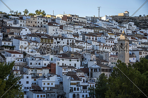 Alcala del Jucar, Spain - October 29, 2016: Panoramic view of typical houses of city during autumn, to the right church of San Andres, take in Alcala of the Jucar, Albacete province, Spain