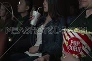 Close shot for young people at Movie Theater whlie Staring at the movie screen, young female is drinking soda and young man holding pop corn.