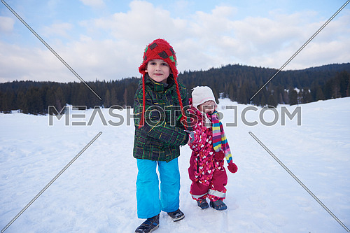 kids walking on snow at winter vacation in forest. happy children group have fun outdoor