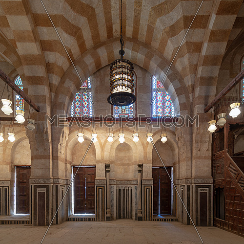 Marble wall with mihrab (Embedded niche), two wooden doors, huge arches, stained glass windows and chandelier at mosque attached to Khayer Bek Mausoleum, Darb Al-Ahmar district, Old Cairo, Egypt