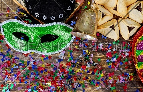 Purim jewish holiday with purim mask and purim a noisemaker on a vintage wood background with kosher wine