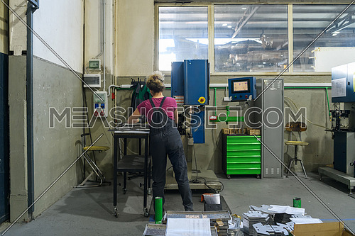 woman wearing a mask due to coronavirus pandemic while working in the modern metal industry and using a drill. High quality photo