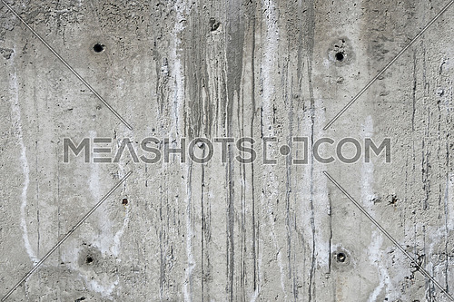 Concrete wall texture with aperture holes, sags and runs of cement at unfinished construction site
