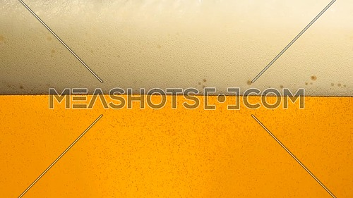 Close up background of pouring lager beer with bubbles and froth in glass, low angle side view, slow motion