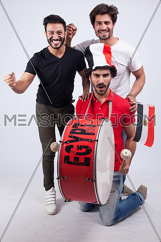 Three young men standing on a white background cheering with a drum for Egypt