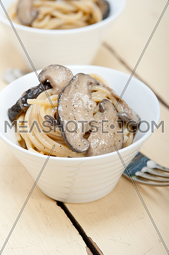 Italian spaghetti pasta and fresh wild mushrooms on rustic wood table