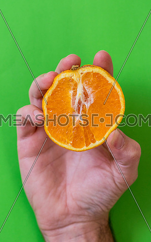 Man's hand holding an orange fruit sliced in half against a green background. Pop art style.