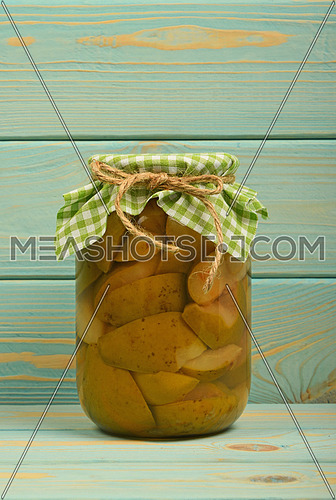 One glass jar of homemade pear compote with green checkered textile top decoration at blue painted vintage wooden surface