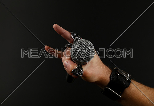 Close up man hand with metal rings and bracelet showing devil horns rock gesture sign, holding microphone over black background, side view