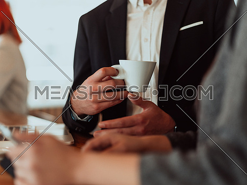 macro photo of a businessman in a suit holding a cup of coffee