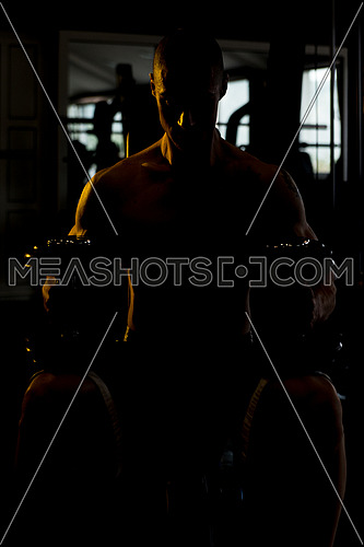 Silhouette Man Standing Strong In The Gym And Flexing Muscles
