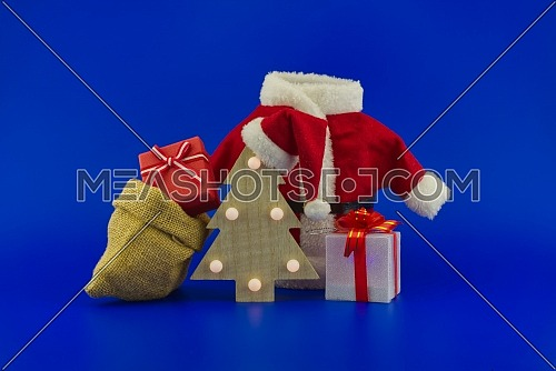 Red Santa Claus suit near wooden Christmas tree with Santa hat and gift boxes on a festive blue background. New Year and Christmas gift season concept