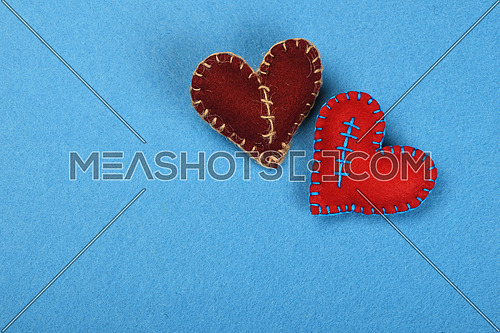 Felt craft and art, two handmade stitched toy hearts, red and brown together on blue background