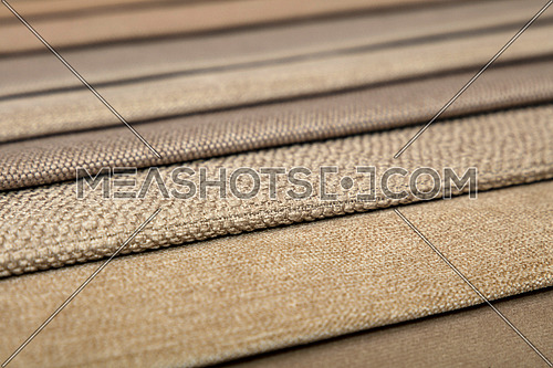 Colorful beige fabric samples swatch in textile catalogue palette, selection of different colors and textures range to choose for interior design and furniture decoration