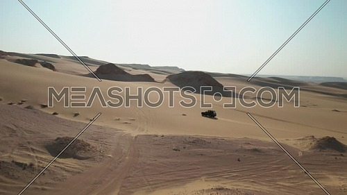 Aerial shot for Two 4x4 Cars moving through sand dunes in the desert at day