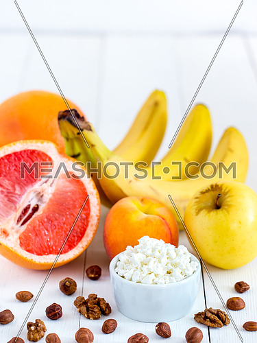 Healthy breakfast: cottage cheese, fruits and nuts on white wooden background. Dieting, healthy lifestyle concept meal. Vertical with copyspace