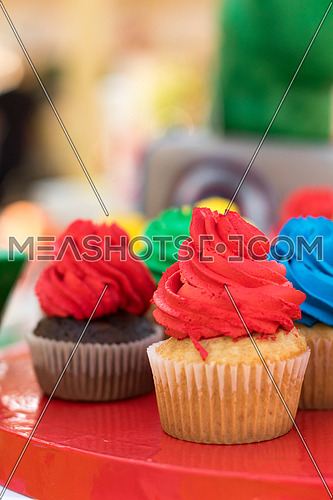 plate full of cupcakes with coloured frosting for kids