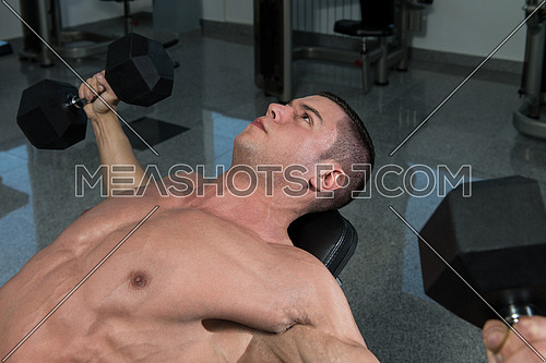 Young Man In Gym Exercising Chest With Dumbbells